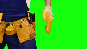 El trabajador saca un destornillador de su correa de la construcción Pantalla verde Cierre para arriba almacen de video
