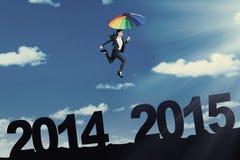 El trabajador salta con el paraguas sobre el número 2014 a 2015 Foto de archivo