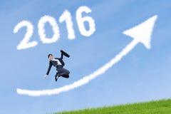 El trabajador salta con números 2016 y flecha ascendente Imágenes de archivo libres de regalías