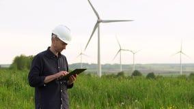 El trabajador se coloca cerca de las turbinas de viento blancas, mecanografiando en una tableta Molinoes de viento, concepto verd almacen de video