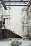 El trabajador se coloca en el andamio de acero y la enyesado del cemento foto de archivo libre de regalías