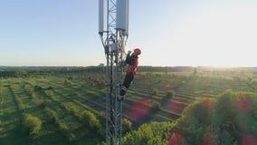 El trabajador sirve la antena celular con el teléfono móvil a disposición, opinión aérea el hombre en casco en el fondo del paisa almacen de video