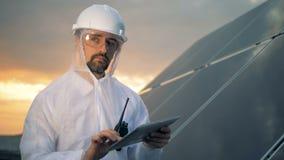 El trabajador solar pensativo se está colocando con un ordenador al lado de una instalación solar en la puesta del sol almacen de video