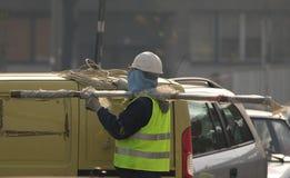 El trabajador toma el cable de extensión del coche Imagenes de archivo