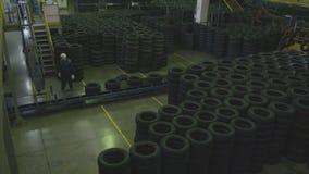 El trabajador toma el neumático de goma del transportador pone el piso almacen de metraje de vídeo