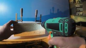 El trabajador toma el taladro de la tabla y perfora varios agujeros en el árbol en Gopro 4K almacen de video