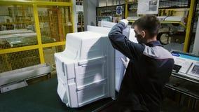 El trabajador toma y lleva el refrigerador los casos internos en la planta metrajes