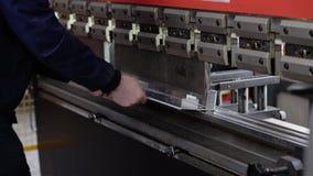 El trabajador trabaja en la dobladora en una empresa industrial Primer de la máquina y de las manos del trabajador metrajes