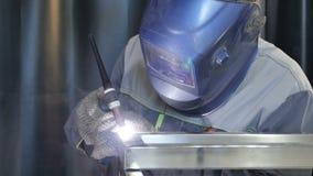 El trabajador utiliza el dispositivo de la soldadura oxiacetilénica en el primer del transportador metrajes