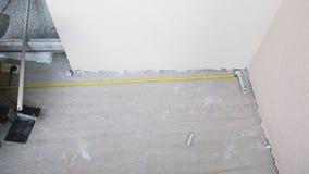 El trabajador utiliza a la cinta métrica mientras que pone los tubos del plástico-metal, trabajador que las medidas riegan los tu almacen de metraje de vídeo