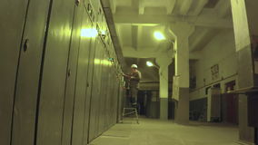 El trabajador va al sitio eléctrico y escribe datos almacen de metraje de vídeo
