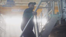 El trabajador va encima de pasos del metal en la cámara lenta del taller espacioso almacen de video