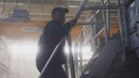 El trabajador va encima de pasos a moler en la cámara lenta del taller metrajes