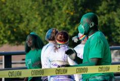 El trabajador verde en un color corre la carrera con la máscara Fotos de archivo