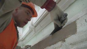 El trabajador vestido en uniforme de la seguridad de construcción enyesa la pared con la herramienta de la espátula almacen de video