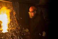 El trabajador vierte el metal derretido del horno en la cucharón Fotos de archivo libres de regalías