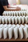 El trabajo bajo pagado en zapato hace la fábrica recoge los deslizadores Imagen de archivo