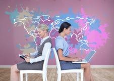 El trabajo de colaboración de las empresarias delante de mapa colorido con la pintura salpicó el fondo de la pared Fotografía de archivo
