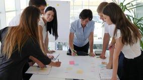 El trabajo de grupo con el personal de sugiere el desarrollo de negocios de las ideas almacen de video