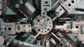 El trabajo de la dobladora del mecanismo del CNC Fabricación de una primavera de alambre Toma panorámica circular de izquierda a