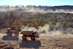 El trabajo de la maquinaria pesada y de los camiones de explotación minera para el transporte de materiales mineros a granel y d fotografía de archivo libre de regalías