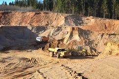 El trabajo de la maquinaria pesada y de los camiones de explotación minera para el transporte de materiales mineros a granel y d imágenes de archivo libres de regalías