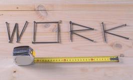 El trabajo de la palabra escrito con los clavos en la madera Fotos de archivo