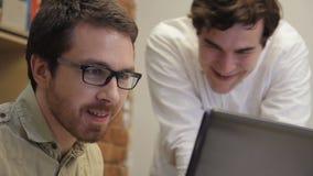 El trabajo de la unidad de la gente joven en oficina sobre proyecto se muestra el primer almacen de video