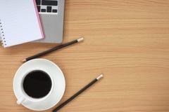 El trabajo de madera de la tabla tiene una taza de café alrededor de un libro en blanco a foto de archivo libre de regalías