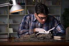 El trabajo del arqueólogo de última hora en oficina imagen de archivo