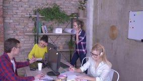 El trabajo diario en oficina, los empleados jovenes trabaja en los ordenadores y hace los expedientes que se sientan en la tabla  almacen de metraje de vídeo