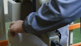 El trabajo embala bolsos en la producción - golpee un saco de grano metrajes