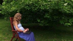 El trabajo embarazada de la muchacha con el ordenador portátil se sienta en silla cerca de árbol de tulipán almacen de video
