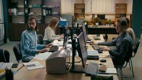 El trabajo en equipo casual joven está trabajando en los ordenadores en la oficina almacen de metraje de vídeo