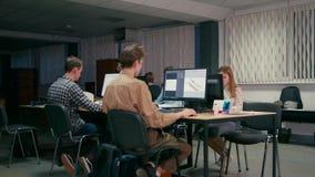 El trabajo en equipo de arquitectos está trabajando en los ordenadores en su comienza para arriba la oficina metrajes
