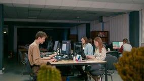 El trabajo en equipo de diseñadores está trabajando en los ordenadores en su comienza para arriba la oficina almacen de video
