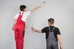El trabajo en equipo de un par está pintando una pared gris Foto de archivo
