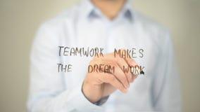 El trabajo en equipo hace el trabajo ideal, escritura del hombre en la pantalla transparente Foto de archivo libre de regalías
