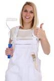 El trabajo femenino joven de la mujer del pintor de casas y del decorador manosea con los dedos encima de la ISO Foto de archivo
