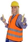 El trabajo femenino joven de la mujer del trabajador de construcción manosea con los dedos encima de aislado Imagenes de archivo