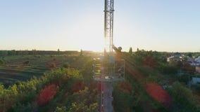 El trabajo a gran altitud sobre la antena celular, hombre en casco aumenta sus brazos para la alegría cuando él ha hecho con éxit almacen de video