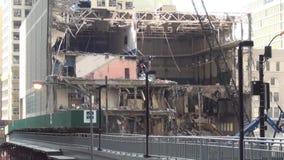 El trabajo grande trabaja a máquina la vieja construcción de destrucción cerca de pocos edificios modernos en una ciudad grande E almacen de video