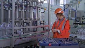 El trabajo pesado del técnico de la mujer en la planta, la hembra sonriente fuerte en workwear y el casco repara profesionalmente almacen de video