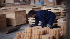 El trabajo sobre el piso de la fábrica embala productos los obreros añaden los ladrillos refractarios para el empaquetado adicion metrajes