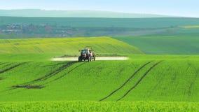 El tractor asperja las plantas en el campo verde metrajes