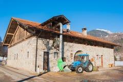 El tractor azul paró al lado de una granja con las paredes rocosas imagen de archivo