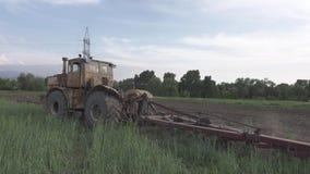 El tractor comienza a arar el campo 4K Perfil plano del pikture almacen de metraje de vídeo