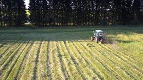 El tractor con el cortacéspedes cortó la hierba del heno en sombra de los árboles almacen de metraje de vídeo
