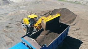 El tractor con un cubo carga una máquina con la arena y escombros almacen de metraje de vídeo