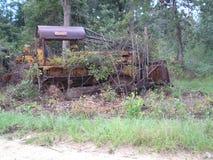 El tractor crecido sobre abandono perdió la naturaleza de la niveladora oxidada fotos de archivo libres de regalías